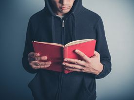 picture of anarchists  - A young man wearing a hooded top is standing around and is reading a red book - JPG