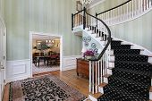 stock photo of entryway  - Foyer in luxury home with carpeted staircase - JPG
