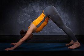 foto of ashtanga vinyasa yoga  - Beautiful sporty fit yogini woman practices yoga asana adhomukha svanasana  - JPG