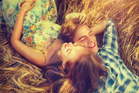 foto of hug  - Beauty Couple Lying and relaxing on wheat field together - JPG
