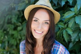 pic of cowgirl  - Happy female in cowgirl hat looking at camera with toothy smile - JPG