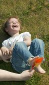 stock photo of tickle  - Laughing child being tickled under the feet with a colorful feather - JPG