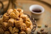 Assorted baklava- A Turkish sweet arranged on  a decorative plate, with arabic black coffee cup in t poster