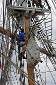 stock photo of yardarm  - A sailor working on the sails high up on the rigging of a sailing ship - JPG