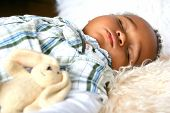 Beautiful toddler of mix parentage sleeping peacefully on sheepskin rug accompanied by his fluffy bunny toy. poster