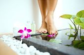 foto of wet feet  - Pair of feminine feet by a sunken foot bath with foot lotion and soap on side - JPG
