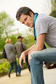 stock photo of sad man  - Young man and walking couple on a blurred background - JPG