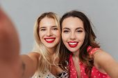 Image of two pretty happy young women posing over grey background. Looking at camera and make selfie poster