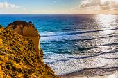 Powerful ocean surf at sunset. The Great Ocean Road. Steep and rocky ocean shore of Australia. The c poster