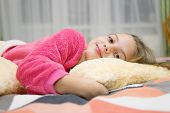 Pajamas And Clothes For Home. Girl Little Kid Wear Soft Cute Pajamas While Relaxing On Bed. Comforta poster