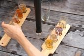 Male Hand Reaching Across A Picnic Table To Grab A Beer Sample From A Selection Of Samples On A Padd poster