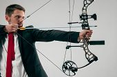 Businessman Aiming At Target With Bow And Arrow Isolated On Gray Studio Background. The Business, Go poster