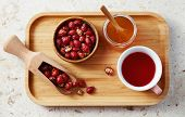 Top view of delicious rose hip tea in cup with dried rose hips on wooden tray.  poster