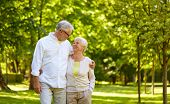 old age, relationship and people concept - happy senior couple hugging in city park poster