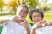Grandma And Grandpa Or Grandparents Make Symbol Of Love By Using Hands And Fingers For Making Hearts poster