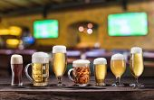 Cold mugs and glasses of beer on the old wooden table. Blurred pub interior at the background. Assor poster