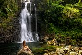 Young Woman In Bikini Sitting By Middle Tavoro Waterfalls In Bouma National Heritage Park On Taveuni poster
