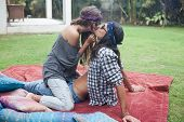 Attractive Young Man Sitting On Blanket On Grass. Beautiful Girl Sits On Top Of Guy And Kisses Him.  poster