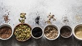 Various Seeds - Sesame, Flax Seed, Sunflower Seeds, Pumpkin Seed, Poppy, Chia In Bowls On A Gray Bac poster