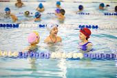 Group Of Little Girls In Swimwear Swimming Together In Indoor Swimming Pool At The Leisure Center poster
