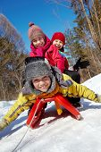 foto of toboggan  - Happy friends in winterwear looking at camera while tobogganing - JPG