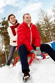picture of toboggan  - Portrait of happy couple tobogganing during winter vacation - JPG