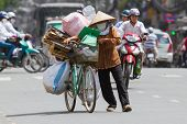 Hue, Vietnam - July 25. Vietnamese Woman Packed Her Possesions On A Bicycle And Is Fleeing For The C