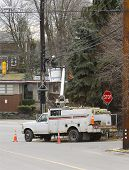 stock photo of boom-truck  - man working on power or communication lines from bucket truck - JPG