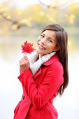 Fall girl holding red Autumn leave outside. Asian woman outdoor portrait in red seasonal autumn coat