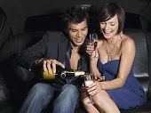stock photo of limousine  - Happy young couple enjoying champagne in limousine - JPG