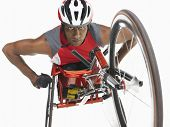 Low angle view of a confident paraplegic cycler against white background