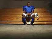 stock photo of bleachers  - Portrait of an American football player sitting on bench with ball - JPG