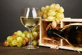 Wooden case with wine bottle, wineglass and grape on wooden table on grey background