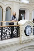Attractive Woman Standing At Railing Near Clock. Waiting