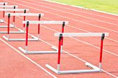 stock photo of olympic-games  - hurdles on the red running track prepared for competition - JPG