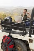 picture of four-wheel drive  - Portrait of young woman using laptop sitting in back of four - JPG