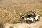 stock photo of four-wheel drive  - Rear view of affectionate couple looking at desert from cliff standing by four - JPG