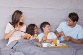 pic of bed breakfast  - Family having breakfast together in bed - JPG