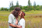 stock photo of hippies  - couple hippie in love kiss on the meadow - JPG