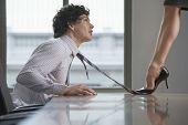 picture of office romance  - Side view of a highheeld businesswoman stepping on businessman - JPG