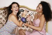 picture of slumber party  - Teenage girls playing with brushes and hair dryer at slumber party - JPG