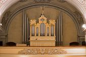 stock photo of pipe organ  - View of the organ in the Catholic church with gold ornaments and angels with trumpets - JPG