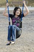 stock photo of kiddie  - young Asian girl wedged in a kiddie swing - JPG