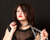 picture of sado-masochism  - beautiful young woman with a chain around his neck on a black background