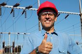 pic of transmission lines  - Thumb up given by smiling engineer next to electrical substation - JPG