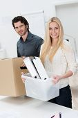 image of possess  - Smiling businesswoman moving into a new office assisted by a handsome male colleague as they carry across her files and possessions in boxes - JPG