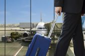 stock photo of low-light  - business man walking travel bag by an international airport - JPG