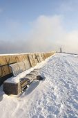 image of boggy  - Blue metal bench on snowy mole and small beacon or lighthouse at the end of the pier - JPG