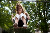 stock photo of swingset  - A child playing on a swingset swinging into the air - JPG
