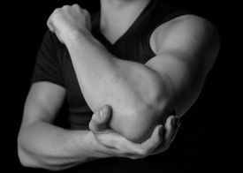 stock photo of elbow  - Man holds his the elbow joint acute pain in the elbow black and white image - JPG